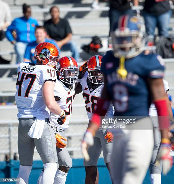 Oklahoma State tight end Blake Jarwin running back Chris Carson and wide receiver James Washington celebrate a touchdown as Kansas safety Fish...