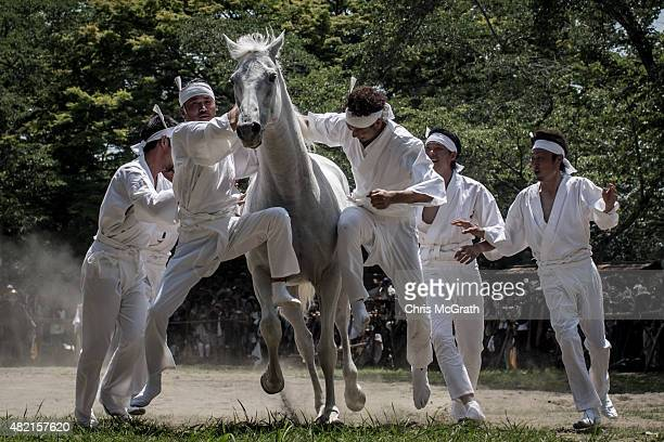 Okobito men try to catch a wild horse in the Nomakake ritual at the Soma Odaka Jinja Shrine during the Soma Nomaoi festival on July 27 2015 in...