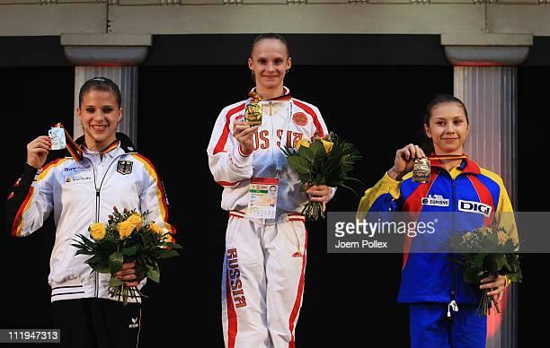 Oksana Chusovitina of Germany for second place Sandra Raluca Izbasa of Romania for first place and Switzerland's Ariella Kaeslin for third place pose...