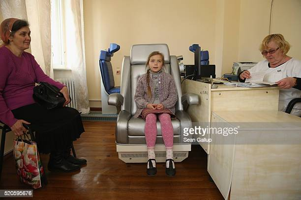 Oksana Kurkach sits in a chair lined with instruments that will analyse her body for radiation emitted from caesium137 as her mother Nadia Kurkach...