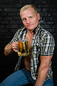Attractive adult man with a beer in the pub.