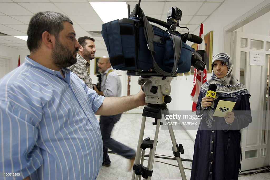Ola Makki (R), a reporter from Al-Manar television, mouthpiece of the Lebanese Shiite Muslim Party of God or Hezbollah, reports 12 August 2004 from the press syndicate in Beirut, where Arab and Lebanese journalists gathered to support the satellite news channel after a decision last month by the French authorities to ban transmission via satellite of Al-Manar programs in France. Lebanese Foreign Minister Jean Obeid described the decision by the Conseil supérieur de l'audiovisuel français (CSA) as a 'political' one, accusing Zionist circles of standing behind the campaign against the TV . AFP PHOTO/Joseph BARRAK