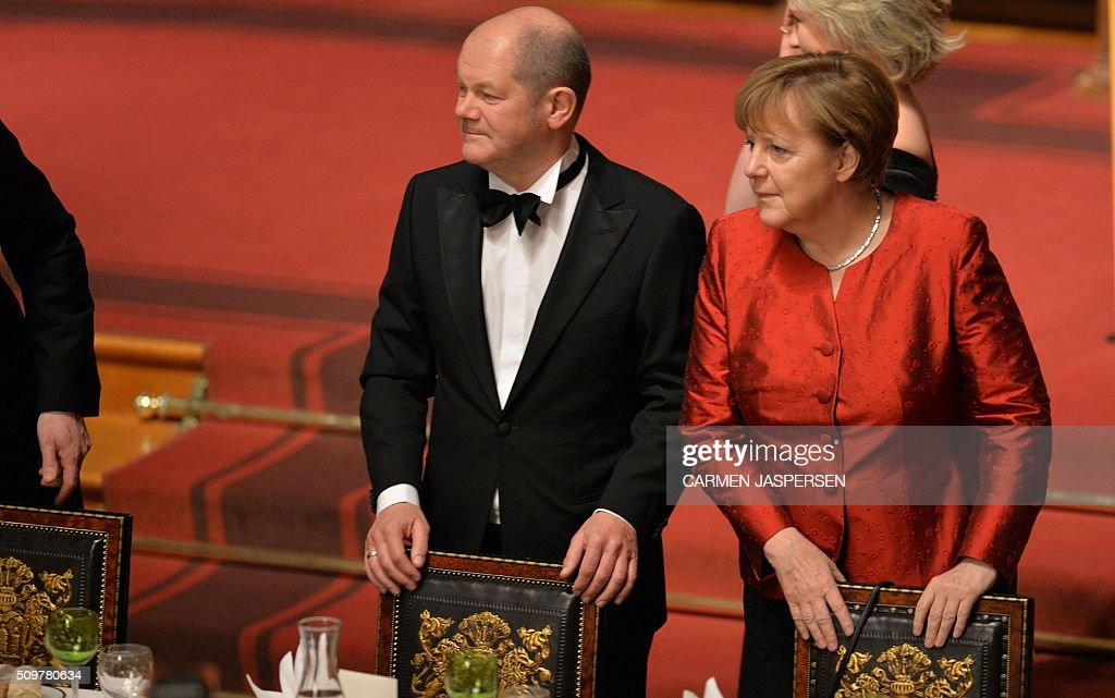 Olaf Scholz, Mayor of Hamburg and German Chancellor Angela Merkel take their seats for the Matthiae-Mahl Dinner in Hamburg, northern Germany on February 12, 2016. / AFP / CARMEN JASPERSEN