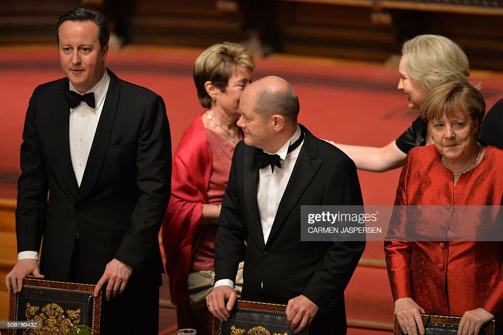 Olaf Scholz (C), Mayor of Hamburg, German Chancellor Angela Merkel (R) and British Prime Minister David Cameron take their seats for the Matthiae-Mahl Dinner in Hamburg, northern Germany on February 12, 2016. / AFP / CARMEN JASPERSEN