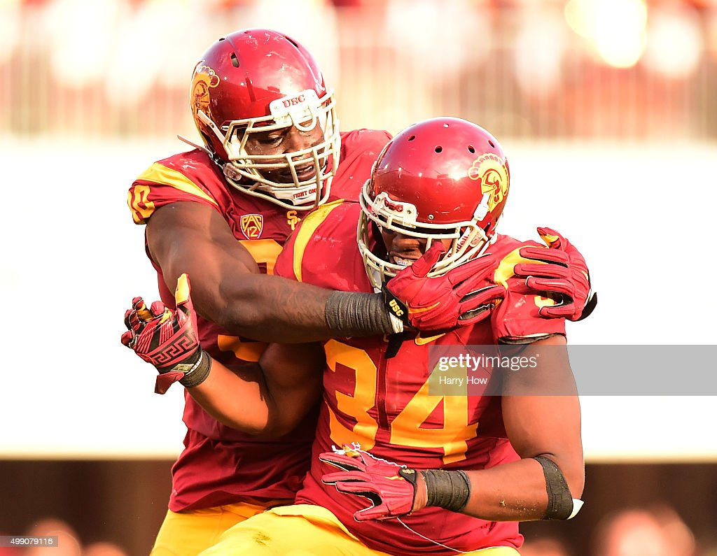 Olajuwon Tucker #34 and Claude Pelon #90 of the USC Trojans celebrate a third down stop of the UCLA Bruins during a 40-21 Trojan win at Los Angeles Memorial Coliseum on November 28, 2015 in Los Angeles, California.