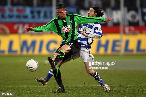 Olcay Sahan of Duisburg tackles Jose Holebas of Muenchen during the second Bundesliga match between MSV Duisburg and 1860 Muenchen at the MSV Arena...