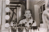 Old 1940s sepia photo of dreamy young woman looking in theater mirror.