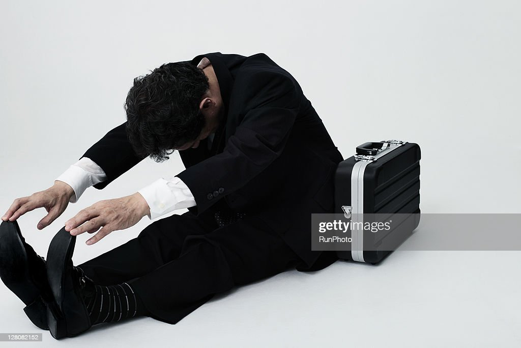 old age businessman stretching