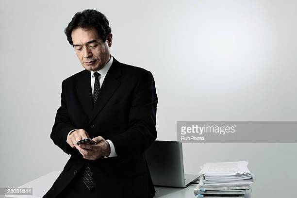 old age businessman touching mobile phone