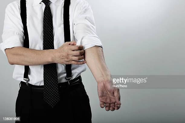 old age businessman turning up cuff on shirt