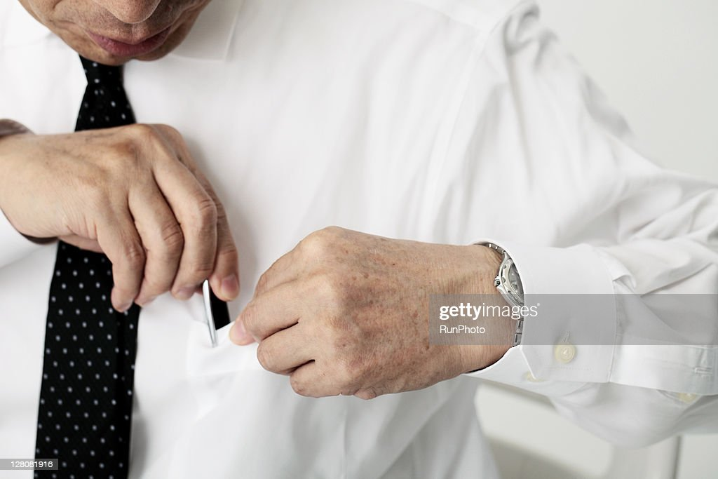 old age businessmen putting a pen in the pocket