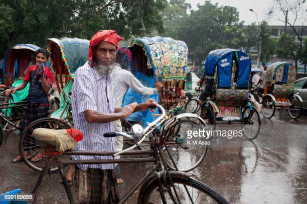 UNIVERCITY DHAKA BANGLADESH Old age rickshaw puller middle in the rain when heavy rainfall made in Dhaka city The death toll rises to 156 in several...