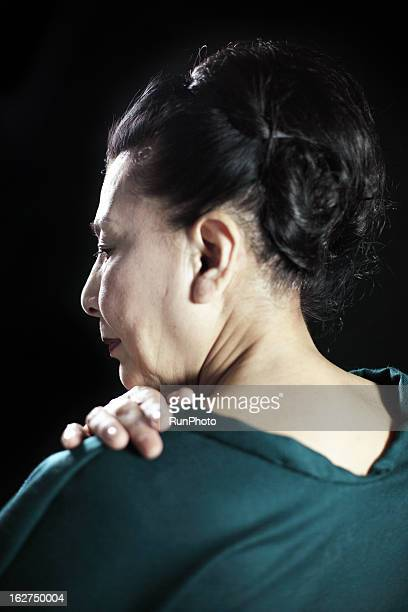 Old aged woman having a stiff neck
