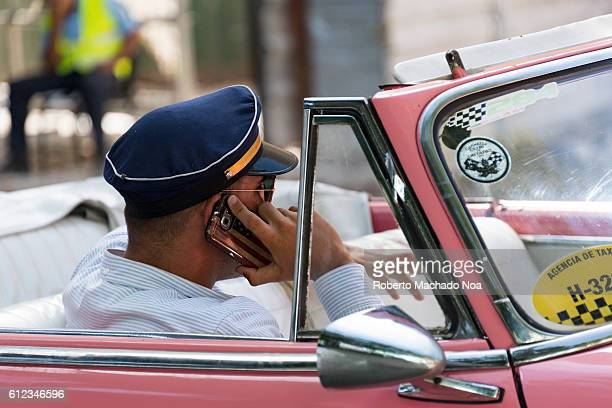 Old american car taxi A uniformed taxi driver making a phone call in an Old American car