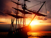 Old ancient pirate ship on peaceful ocean at sunset. Calm waves reflection, sun setting.