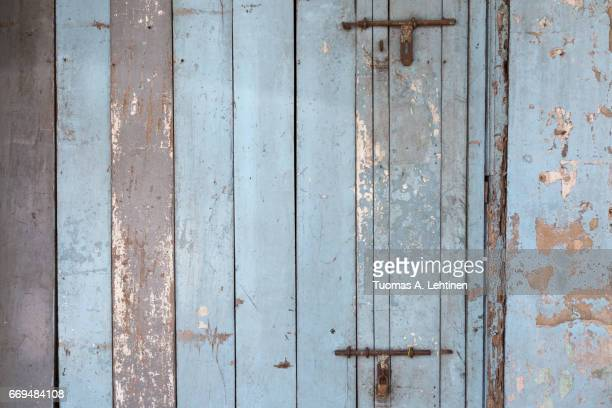 Old and faded light blue wood board wall or door texture background.