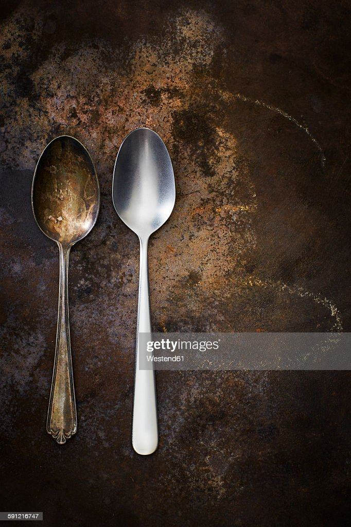 Old and modern spoon side by side on rusty ground