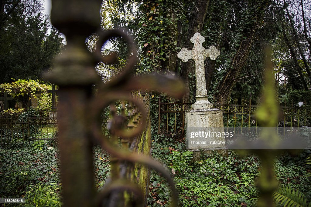 Old and weathered gravesite on a graveyard, on November 7, 2013, in Berlin, Germany. Stony cross on a cemetery.