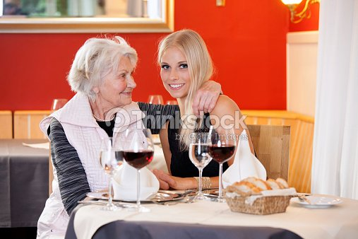 Old And Young Women At Table Having Snacks Stock Photo