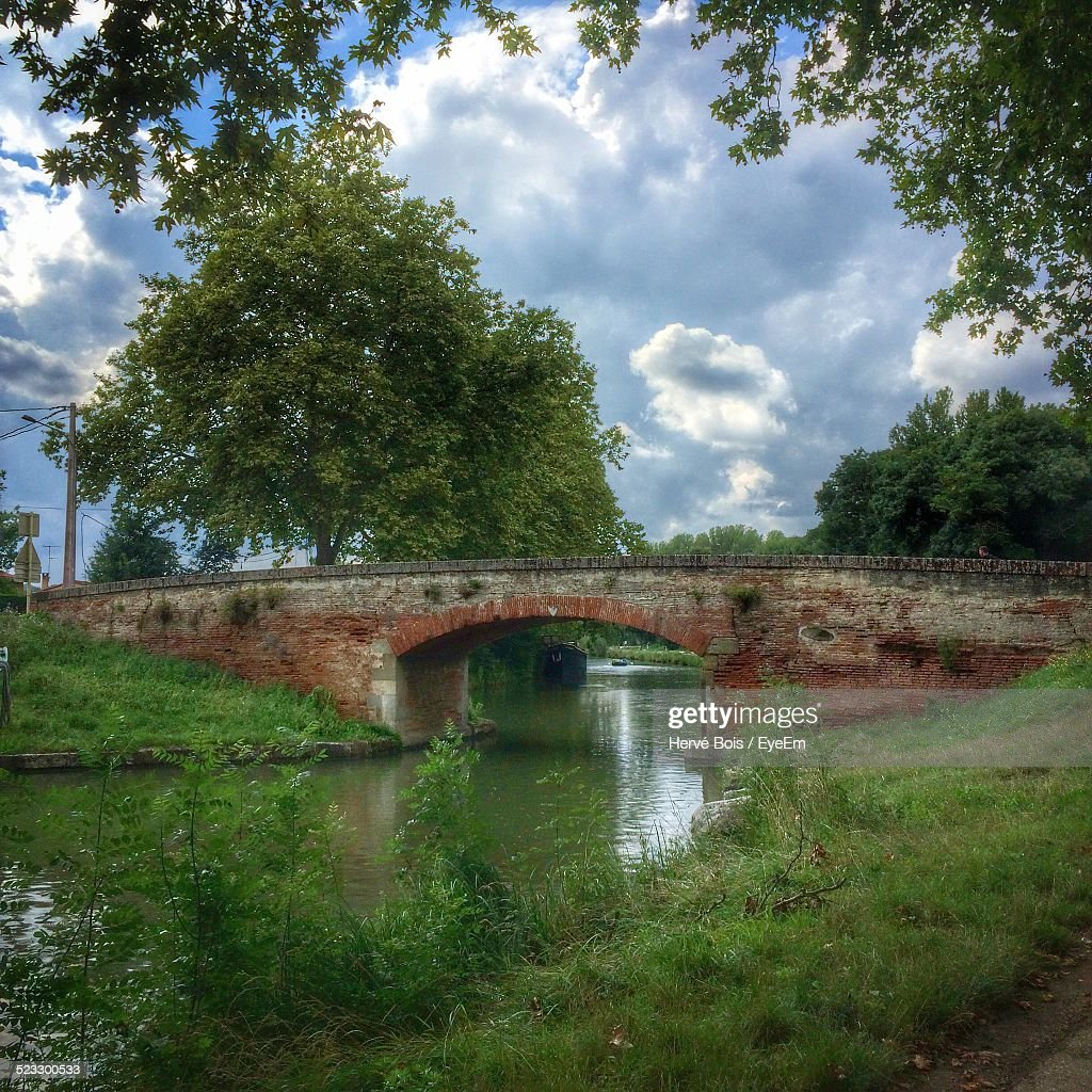 Old Arch Bridge Over Canal Against Cloudy Sky
