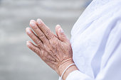closeup old Asian female hand praying in a temple blessing from Buddha