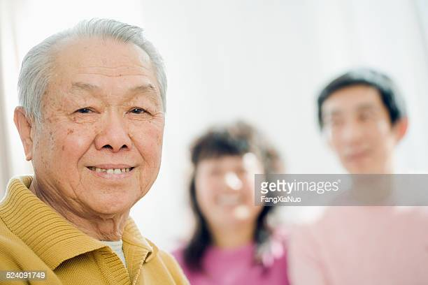 Old Asian man smiling with family