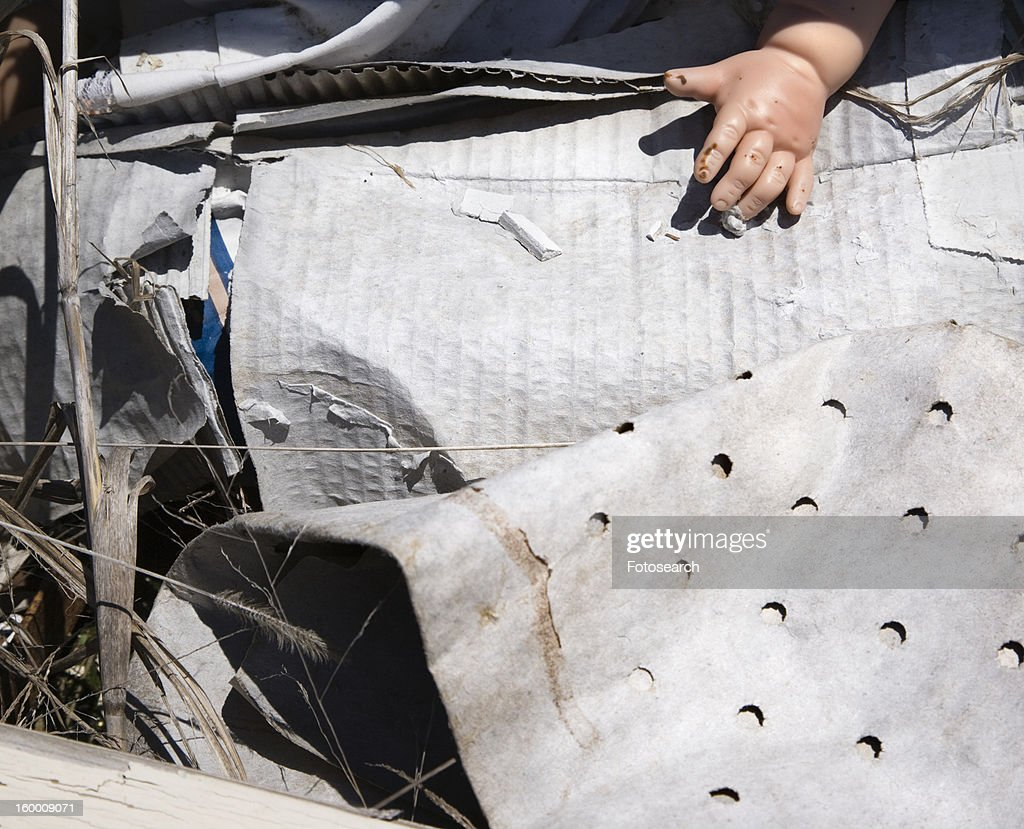 Old baby doll hand sticking out of garbage at landfill. : Stock Photo