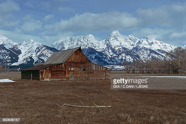 Old barn with the high peaks of the Teton Range in the background Jackson Hole Grand Teton National Park Wyoming United States of America
