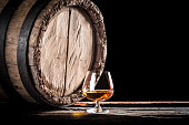Old barrel and a glass of cognac.