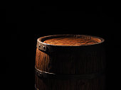 Old barrel with cognac on wooden backgroun.