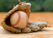 Close up detail of an old, worn baseball and leather glove laying on home plate, surrounded by clay