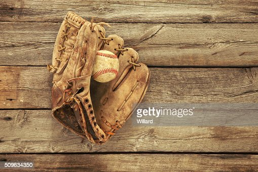 Old baseball and mitt on rough wood background : Stock Photo