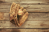 Vintage baseball mitt and ball on grungy, rough wood background viewed from above