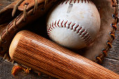 A top view image of an old used baseball, baseball glove, and wooden bat.
