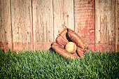 Old leather baseball mitt and ball on grass field against a rough wooden fence