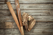 Old baseball with mitt and bats on rough wood surface