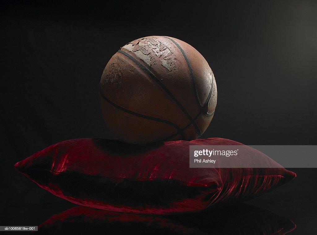 Old basketball on velvet cushion