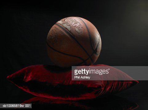 Old basketball on velvet cushion