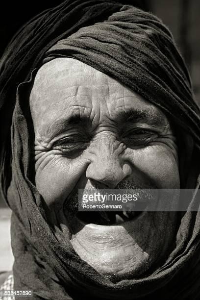 Vieux berbère rire regardant l'appareil photo noir blanc