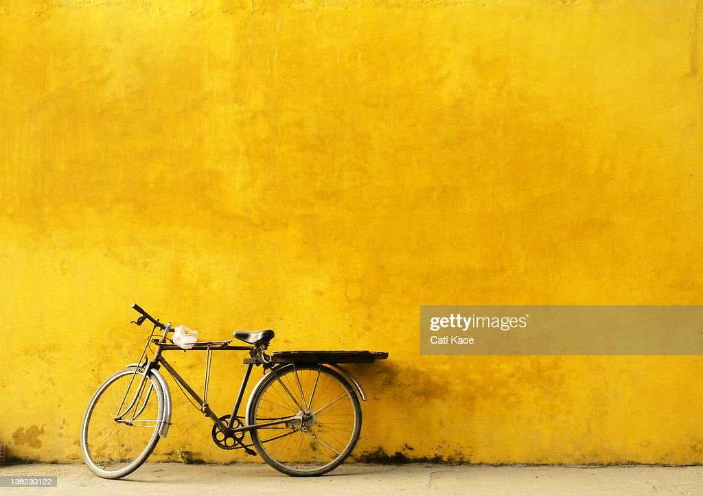 Old Bicycle parked against worn yellow wall : Stock Photo