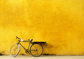 Old Bicycle parked against worn yellow wall