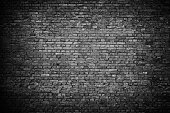 Black rough brick wall background. Grunge texture. Vintage wallpaper.