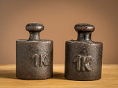 Old black iron 1kg weights for a kitchen scale standing on a table