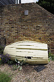 An old and broken rowing boat leaning against a brick wall.