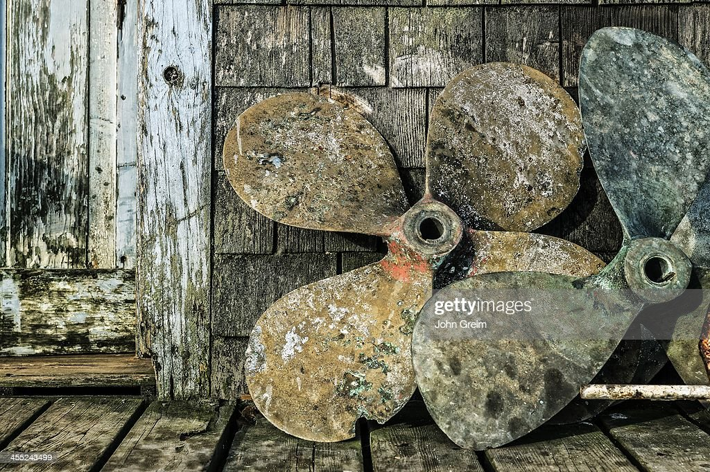 S VINEYARD, MENEMSHA, MASSACHUSETTS, UNITED STATES - : Old boat propellers on a fishing village dock.