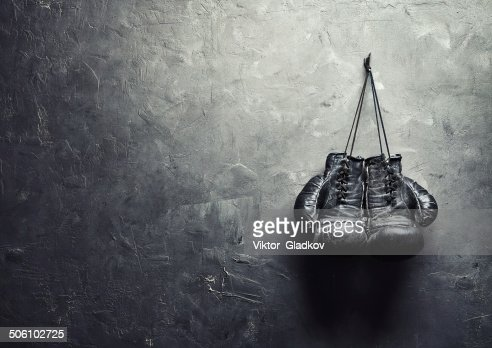 old boxing gloves nailed to the textured wall : Stock Photo