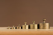 Old brass weights for a kitchen scale standing on a table