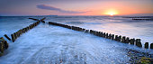 Old Breakwater on Beach at Sunset
