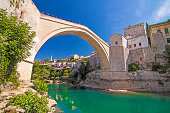 Old Bridge (Stari Most), UNESCO World Heritage, and emerald river Neretva among rocks and old city buildings in summer sun lights. Mostar, Bosnia and Herzegovina