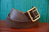 brown retro leather belt at the green wall